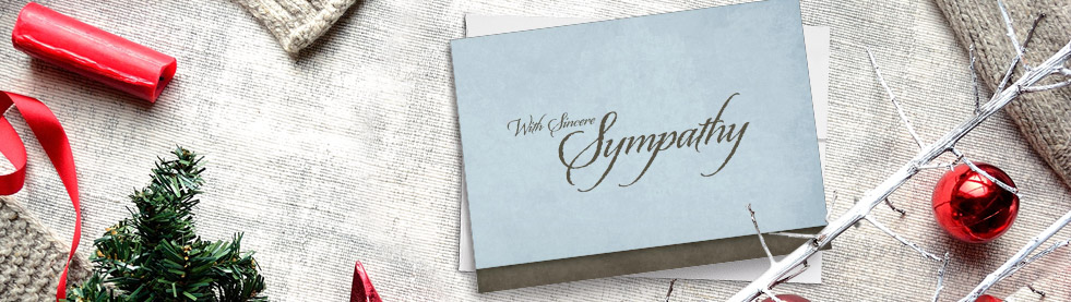 Blue sympathy card lain among Christmas objects like red ribbon, ornaments, and foliage.