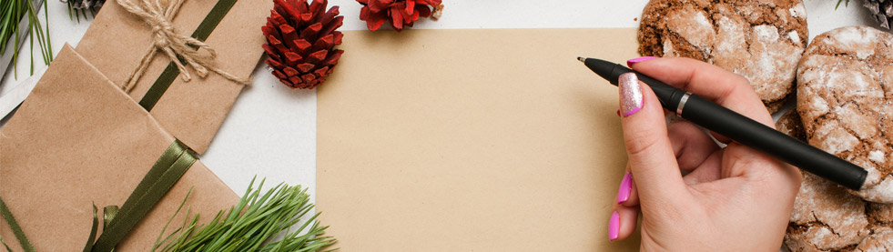Long image of a female hand starting to write on a brown Christmas card with seasonal accents like pine sprigs, pine cones., cookies, and packages.