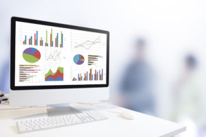 Modern desktop computer showing various multicolored graphs, with out of focus human figures in the background.