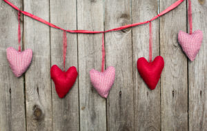 Five pink and red fabric hearts hang down against a woodgrain background.