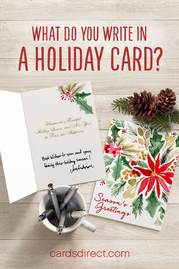 "An open and closed version of a floral holiday greeting card is lain against a woodgrain table. Other objects like a mug full of pens, pine cones, and pine needles add subtle seasonal accents, with the words 'What do you write in a holiday card?"" written above the items in red. Cardsdirect.com - the company name - is written below the arrangement in red."