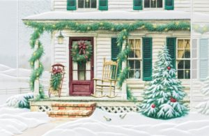 An inviting country home, during the holiday season, is decorated with wreaths, garland, a sled, a rocking chair, and a Christmas tree with red ornaments. The house sits in a snowy front yard with a small fence in the background.