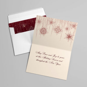 Alternative views of a greeting card - one inside the envelope with its red cover sticking out - the other view is the open card with red snowflakes trailing down the top fold and a red verse written on the bottom fold. The verse reads 'May peace and joy be yours at this holiday season and throughout the New Year'.
