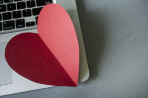 A big red construction paper heart sits at the bottom-right-hand corner of a laptop computer.