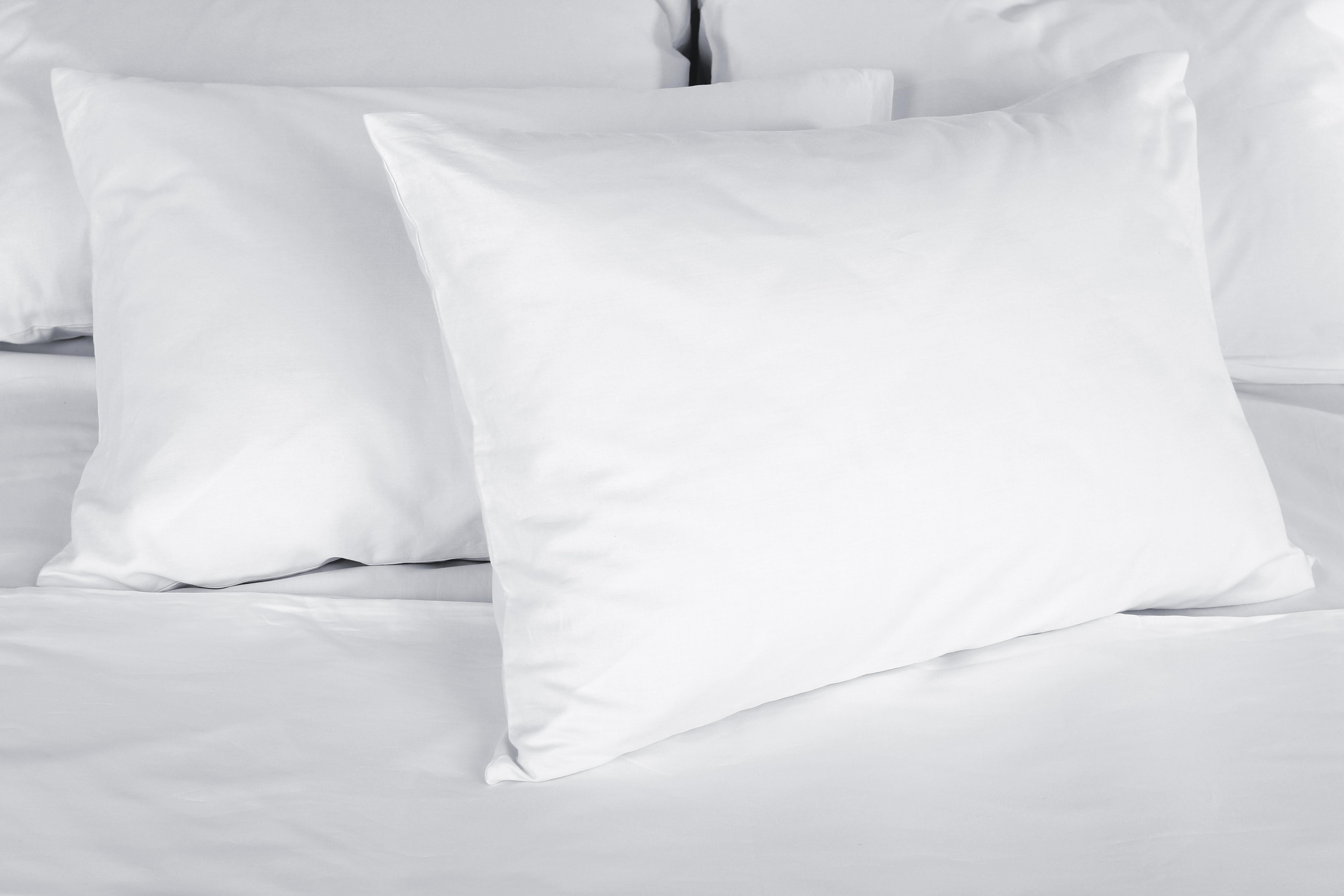 Fluffy white pillows across a soft white bed.