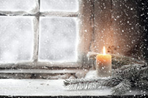 A lit candle rests among sporadic pine branches, by an old wooden window, as snow falls around it.