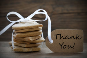 A stack of delicious light brown square-shaped cookies tied with a white ribbon and complimented with a light brown gift tag that reads 'thank you' in black letters, all against a woodgrain background.