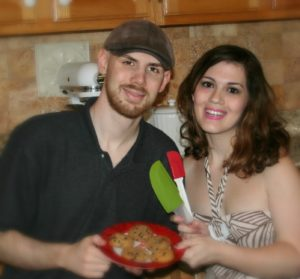 A happy male and female couple holding a plate of homemade cookies in the kitchen.
