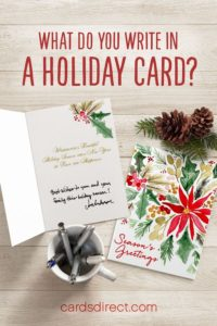 Floral Christmas cards on a table with pine cones, mug, and pens; the text above reads 'What do you write in a holiday card?' in red.