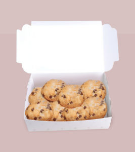 A delicious batch of chocolate chip cookies with coconut on top, in a white bakery box, against a soft pink background.