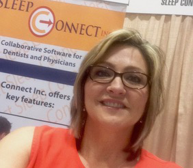 Selfie of a middle-aged blonde woman in glasses and a coral-colored shirt, standing in front of a curtain and a billboard advertising for a company called Sleep Connect, Inc.