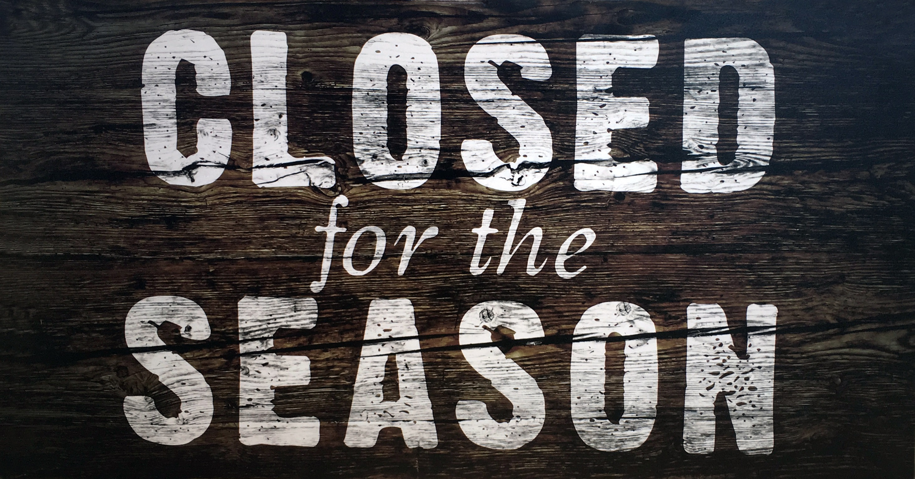 'Closed for the Season' is written in white paint against a wooden sign.