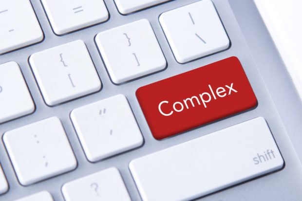 Close-up of a computer keyboard with a red 'enter' key that has been replaced with the word complex.