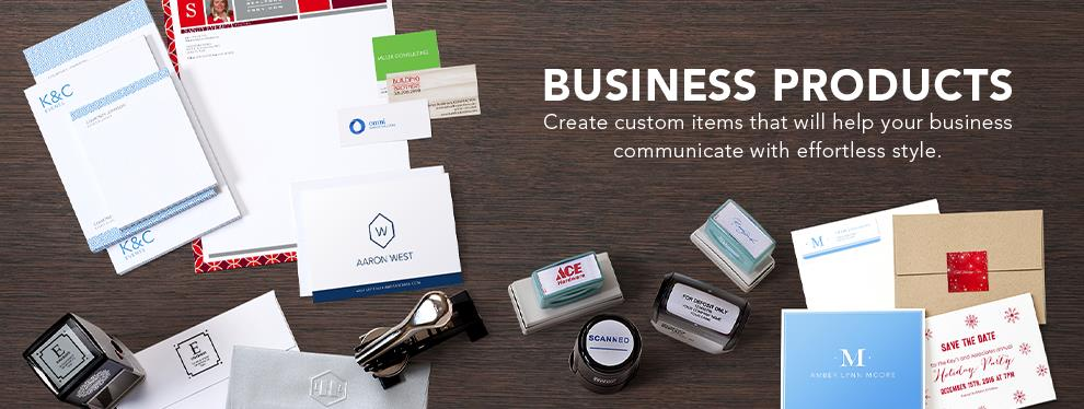 A wide range of business products, such as personalized notepads, ink stamps, an embosser, envelopes with labels, greeting cards, and business cards lay against a woodgrain background. Amidst the products, the words ''Business Products • Create custom items that will help your business communicate with effortless style.' are written in white.