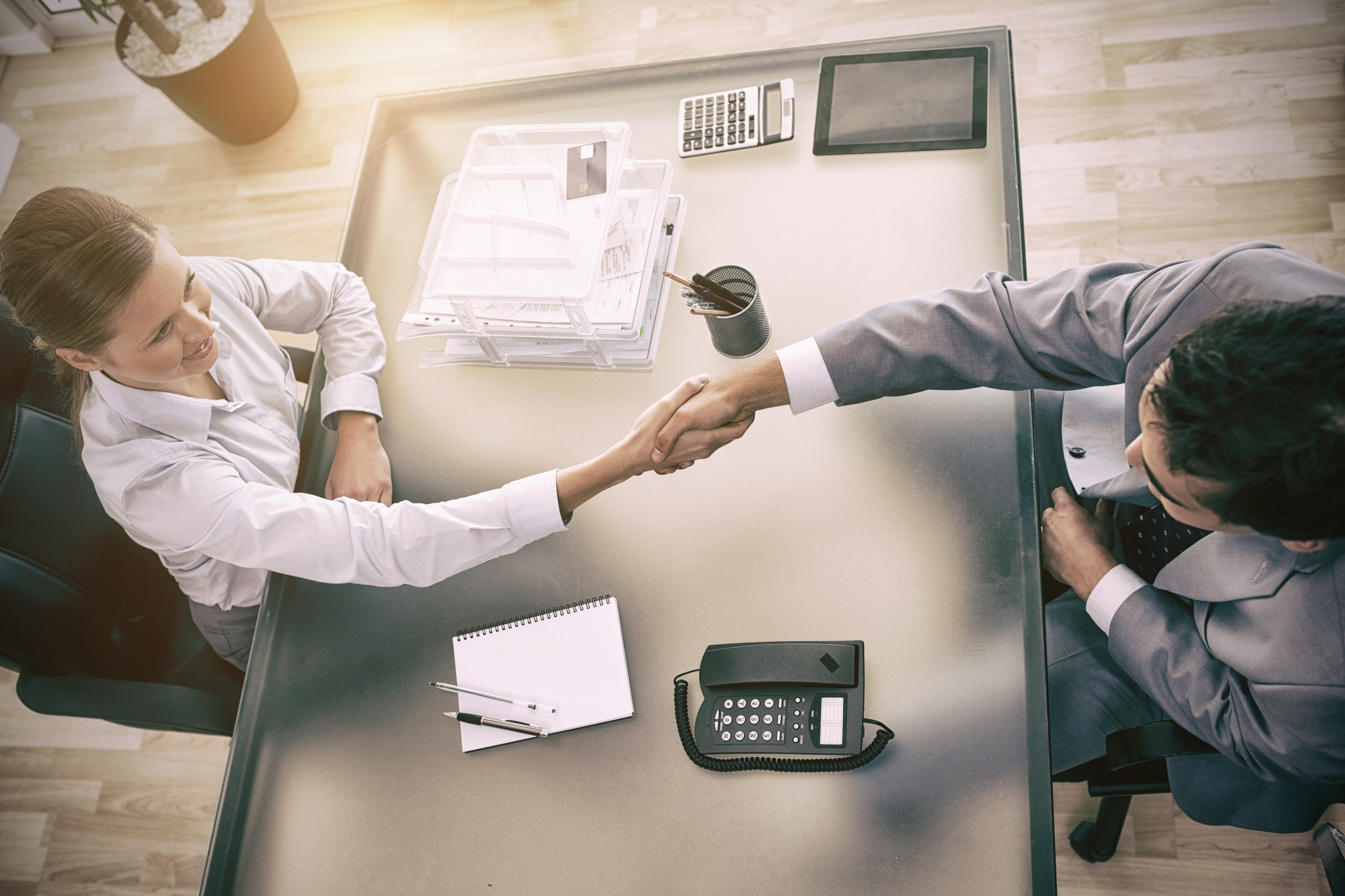 Aerial view of a modern business meeting between a man and a woman, shaking hands from two opposing sides of a desk.