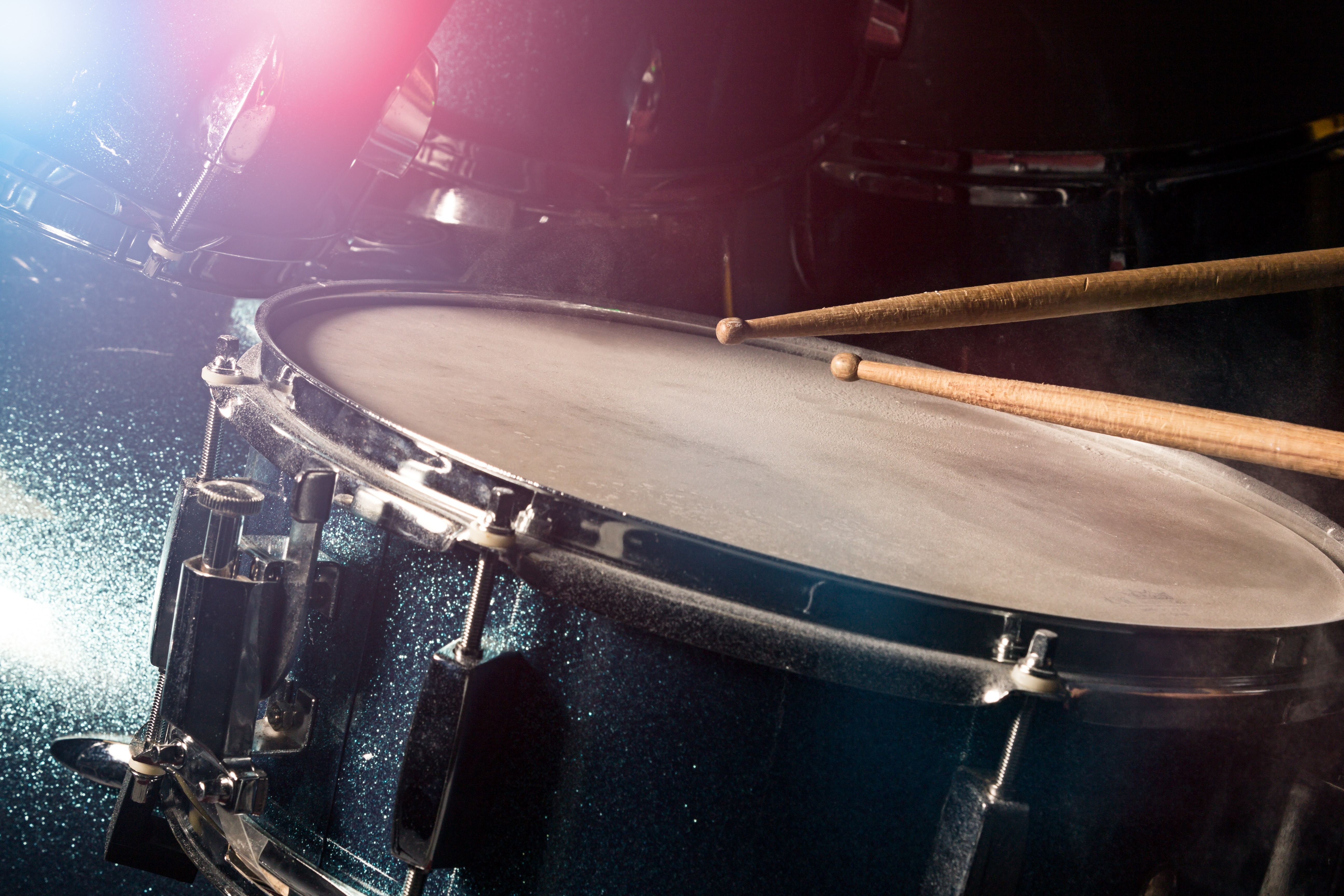 Close-up of drum stick hitting a drum. Florescent pink and blue lights can be seen in the background.