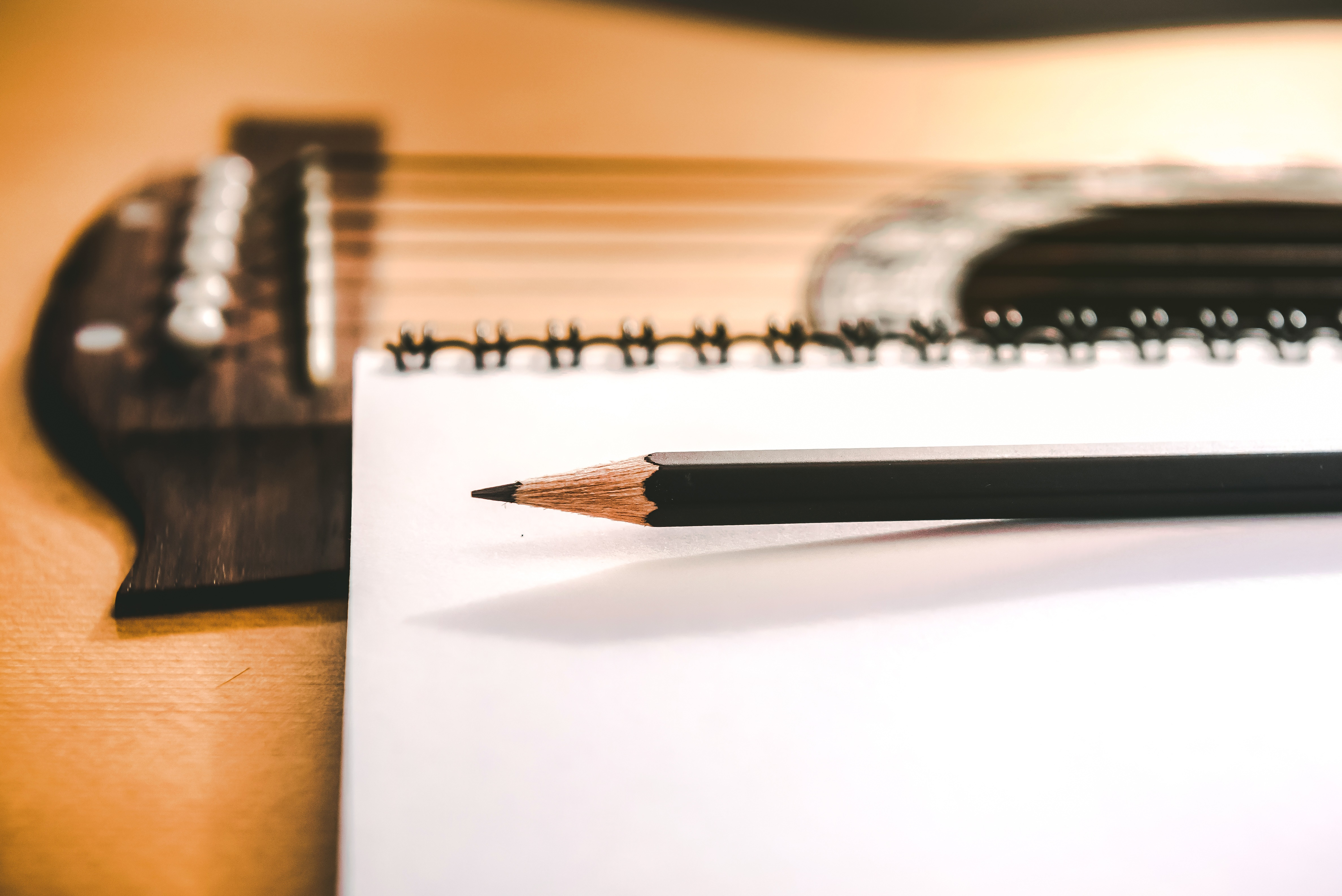 Close-up of a clean white notebook with a freshly sharpened black pencil siting on top of an acoustic guitar.