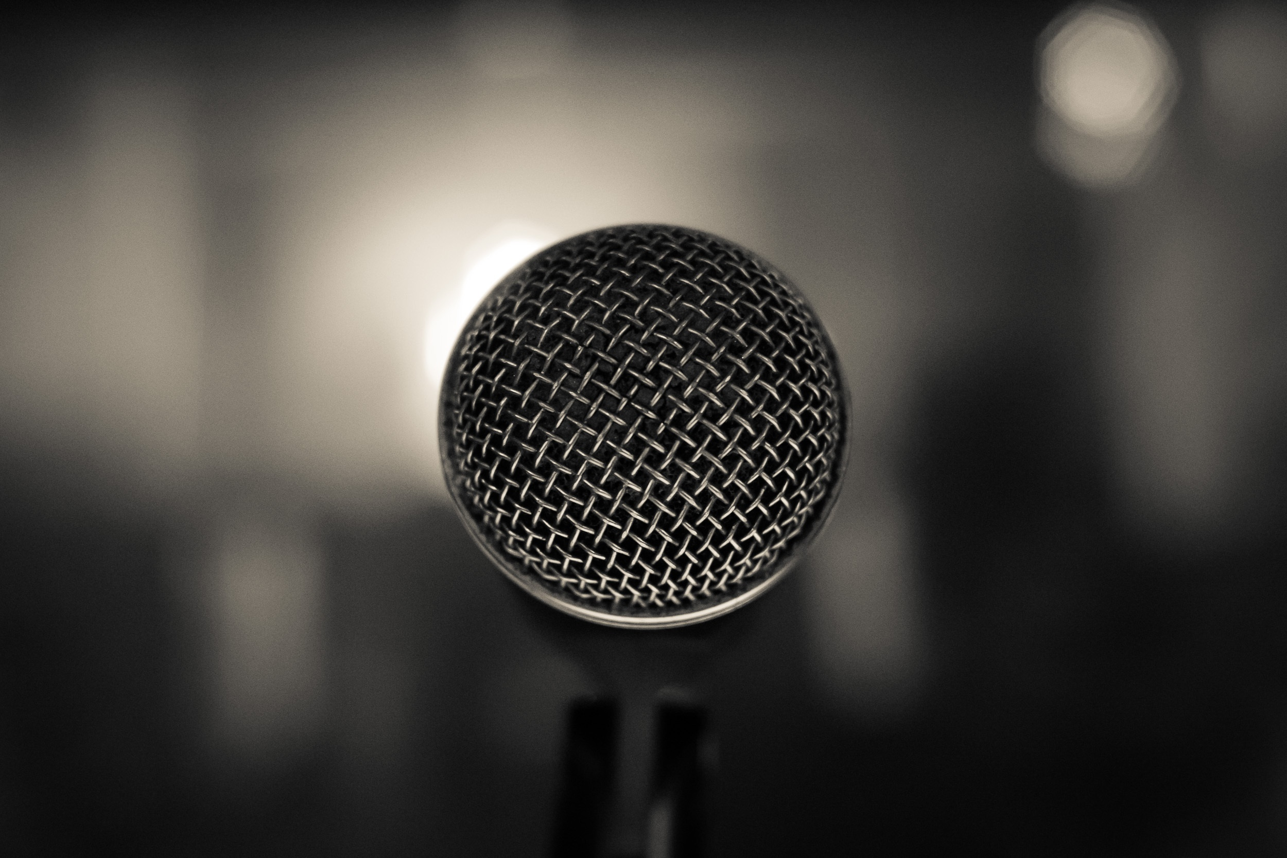 Close-up of a standing microphone with an out-of-focus black and white background.