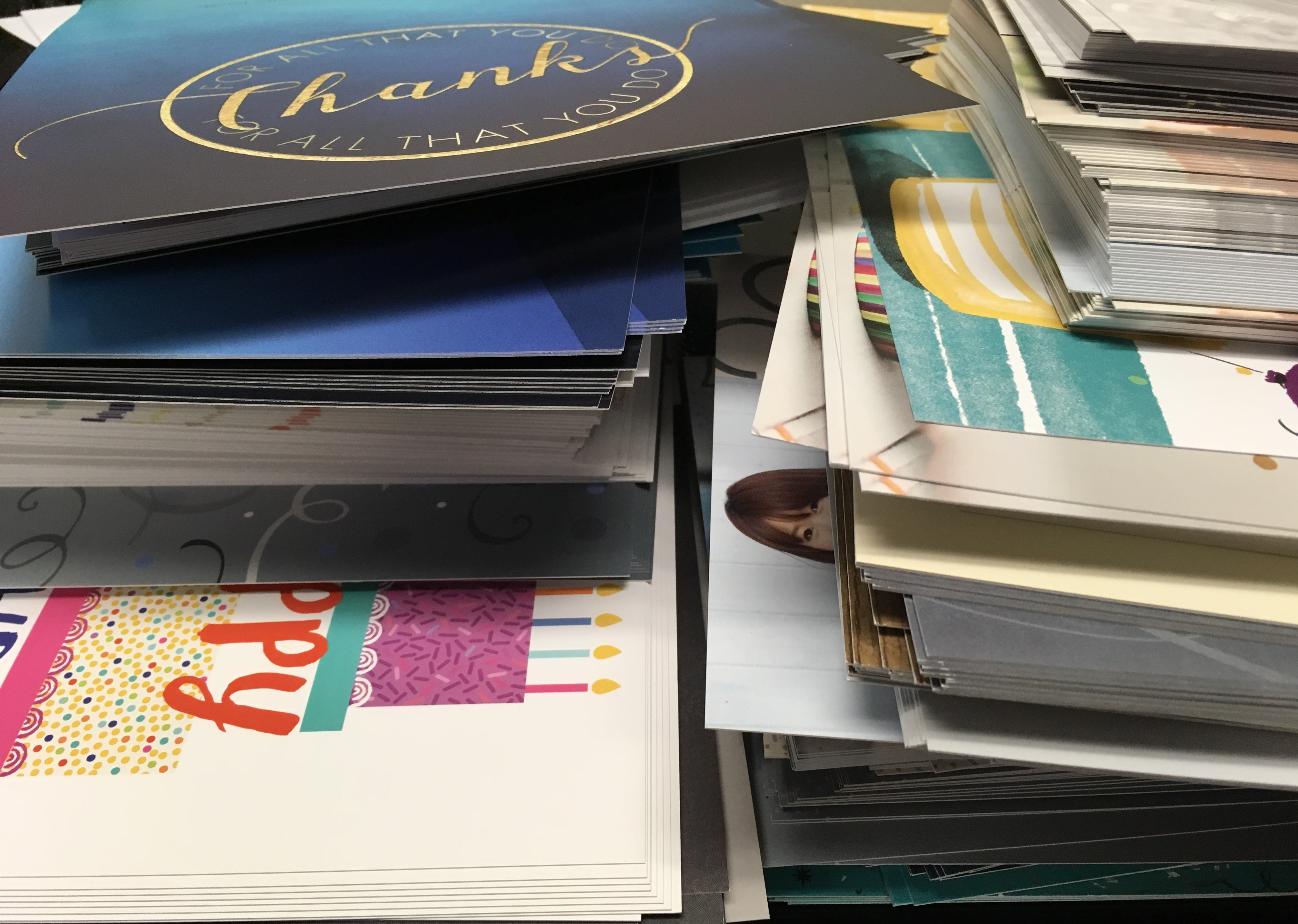 A large pile of various greeting cards in different colors.