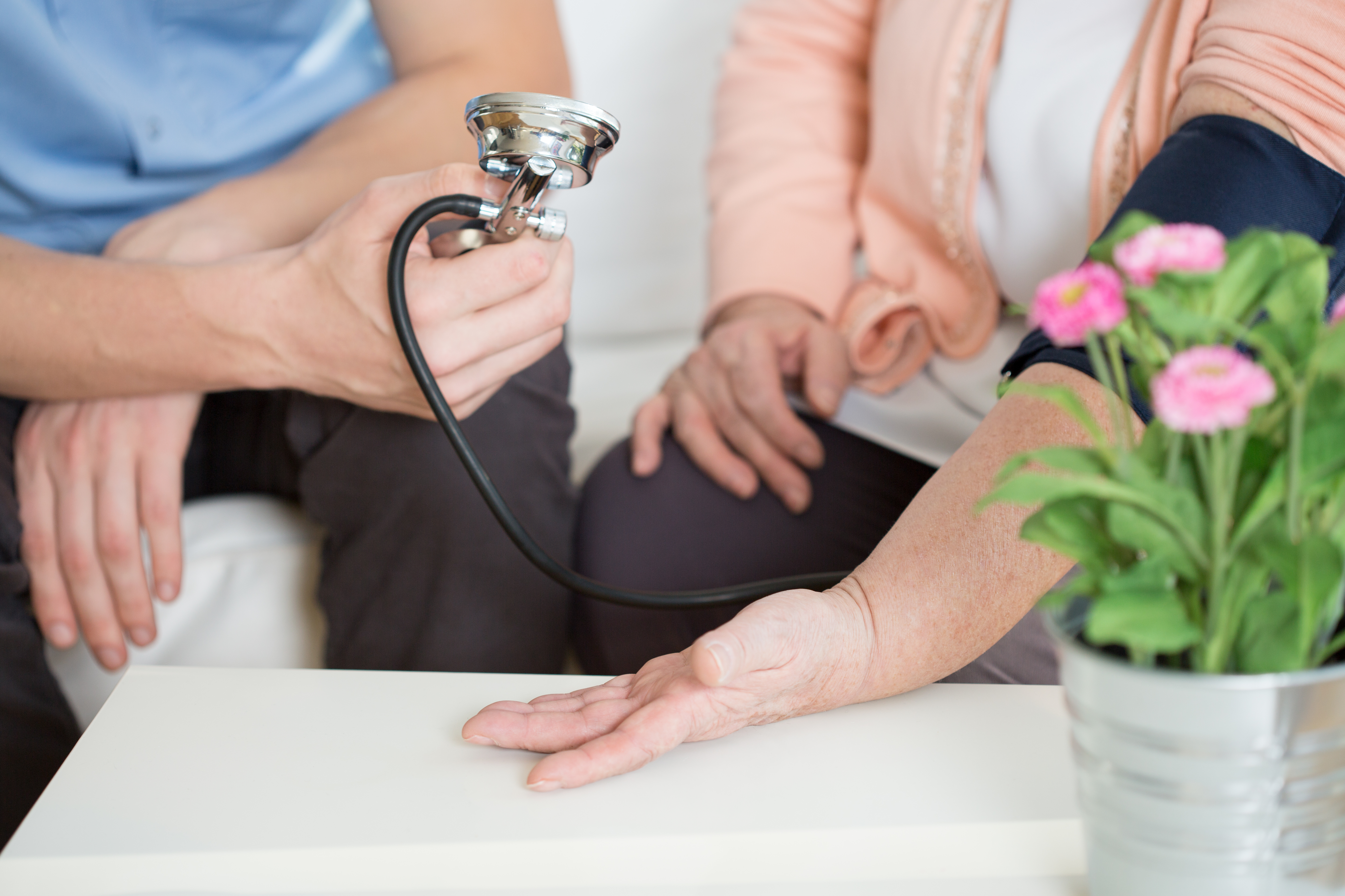 Close-up photograph of a male nurse taking and elderly female's blood pressure.