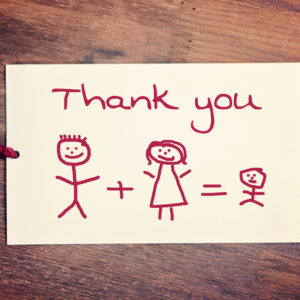 Three stick-figures are drawn in red under the words thank you - a dad plus a mom equals a child.