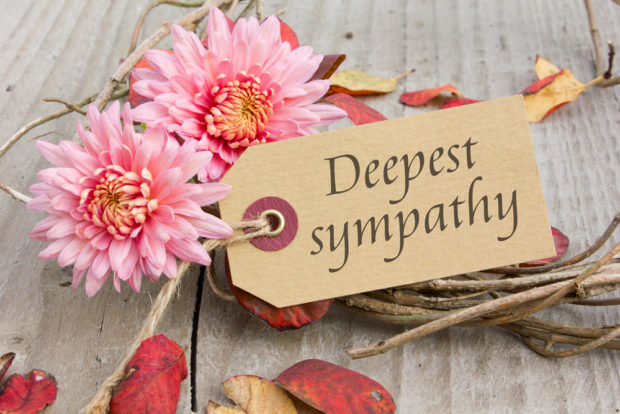 Attached to a bouquet of pink flowers and twigs with twine is a small brown tag that reads 'Deepest sympathy.' Dried red and brown leaves are scattered about a wood-grain background.