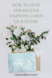 Light colored floral arrangement with a blue marble sympathy card and a message in green that reads, How to Send and Receive Sympathy Cards Graciously.