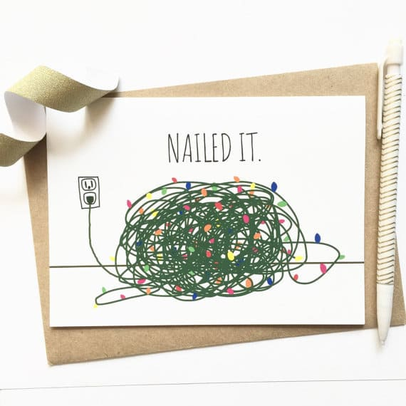 A hand-drawn greeting card featuring a pile of tangled Christmas lights with the words 'Nailed It' above it. The card lays against a brown envelope, and is accented with a bit of ribbon and a decorative pen.