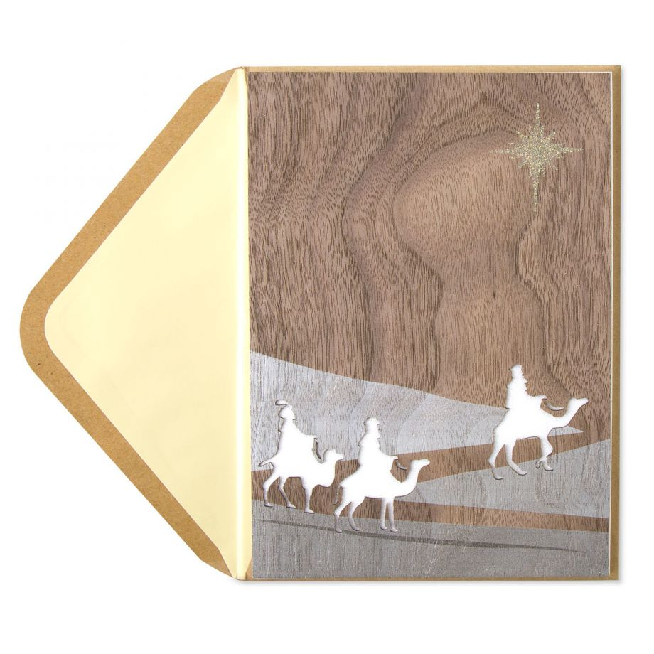 This wood-grain greeting card features the three wise men traveling through the desert with the North Star gleaming above.