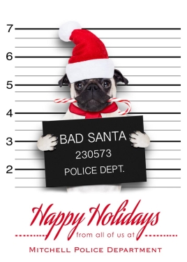 A pug, wearing a Santa cap and chewing on a candy-cane, is receiving a mugshot. The text below him reads 'Happy Holidays' in red letters.