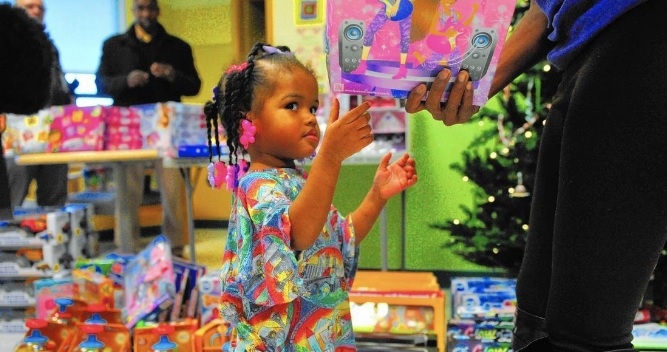 Small African American girl in a colorful outfit surrounded by toys in a Children's Hospital.