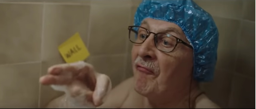 Elderly man sitting in a bathtub with a blue shower cap on.