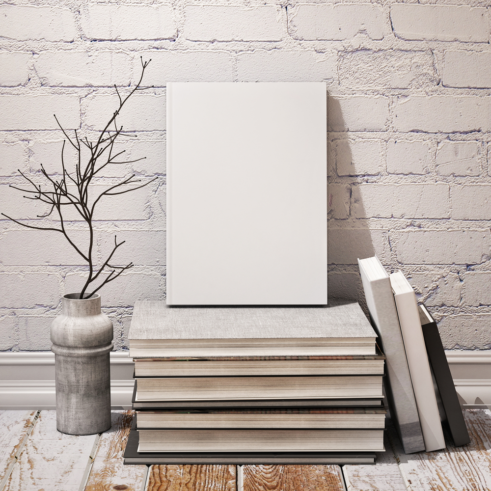 A shabby chic scene shows books in black, gray, and white tones, as well as some twigs inside a vase in similar hues, sitting on wooden floor that is partially painted white and leaning against a white brick background.