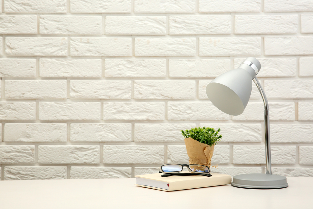 A light-silver lamp, a beige book, black-rimmed glasses, and a green plant sit on a light-colored desk against a white brick background.