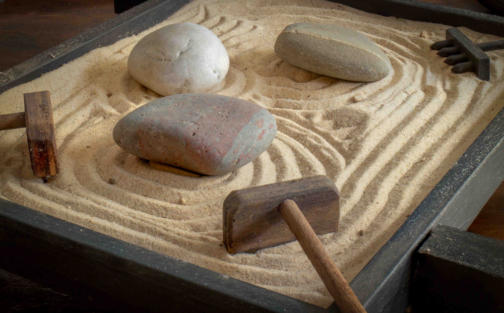 Rocks and rakes in a miniature sand garden with a maze-like design drawn into it.
