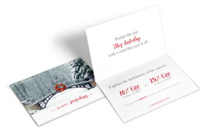 Exterior and interior shots of a holiday greeting card with a winter landscape on the front that includes a bridge with red wreath.
