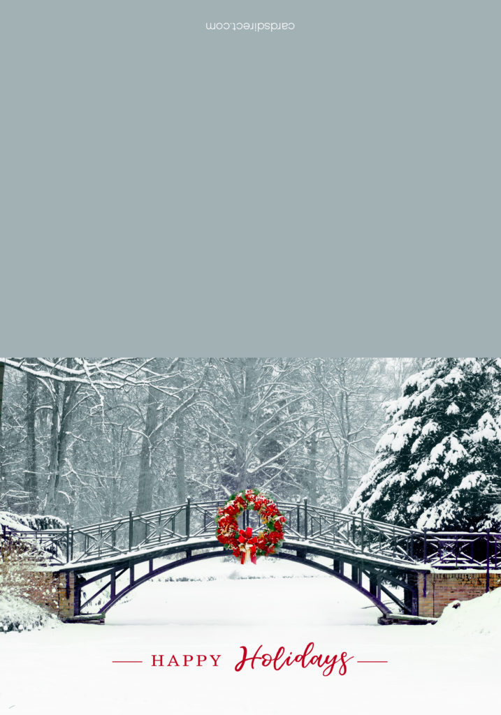 A red wreath on a bridge crossing over a snowy pond on the front of a greeting card.