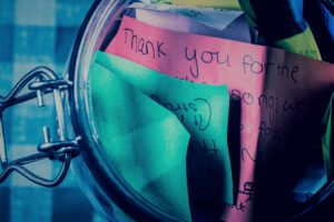 A mason jar, resting on a gingham table cloth, open with thank-you messages inside. The messages are written on different colored pieces of paper.