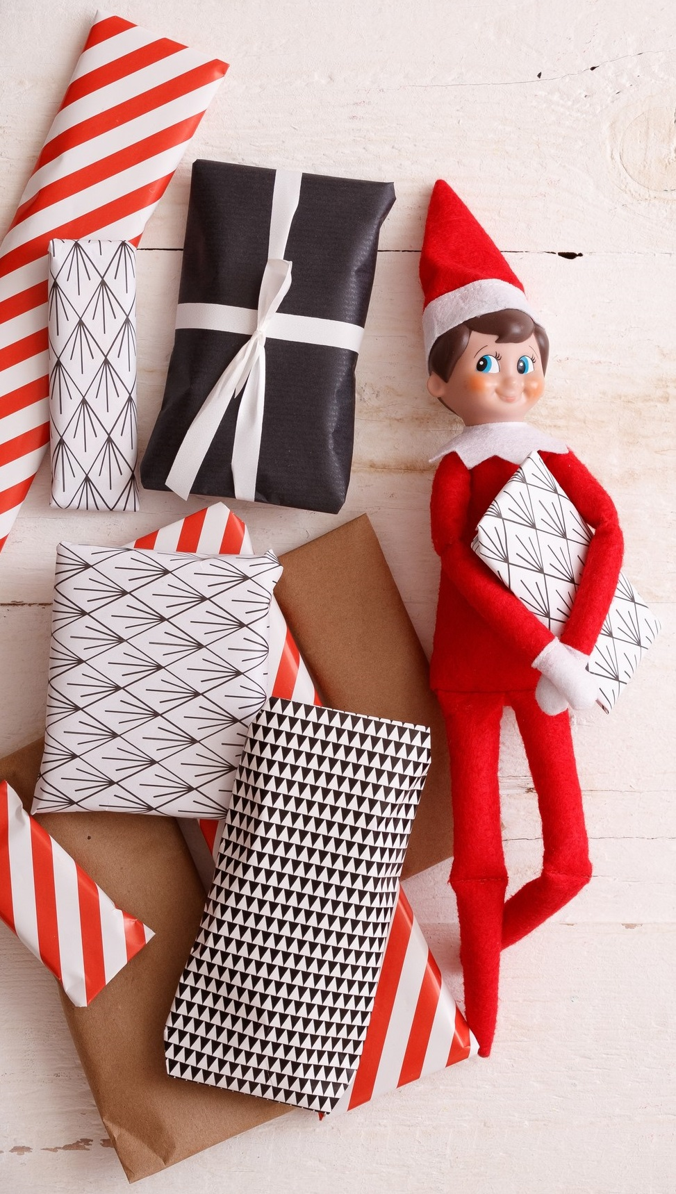 Closeup of Elf with advent presents on white wooden background. Christmas and Holiday concept