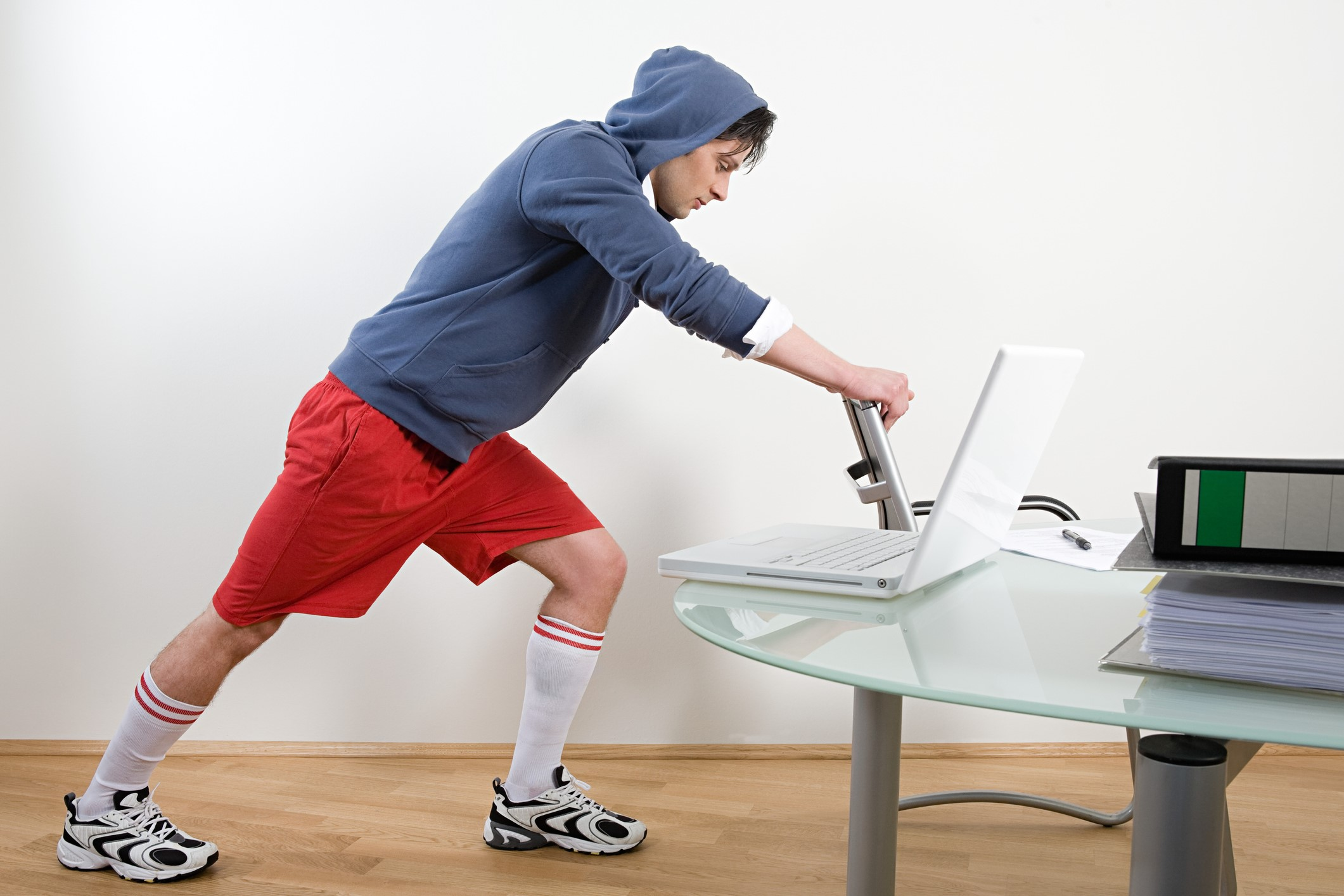 Man stretching with a chair at the office in  red gym shorts.