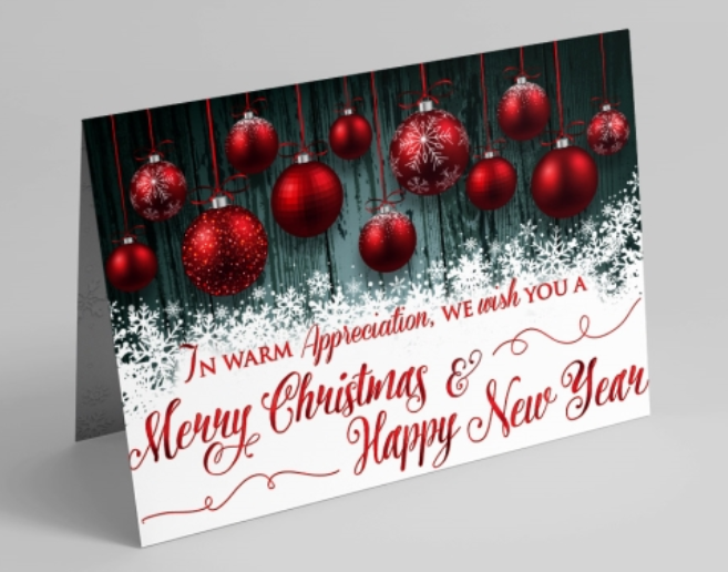 This card features gorgeous red ornaments with snowflake accents against a dark teal wood-grain background that rests above a pile of snowflakes. In the snowflakes, a message reads 'In Warm Appreciation, We Wish You A Merry Christmas & Happy New Year' in red letters.