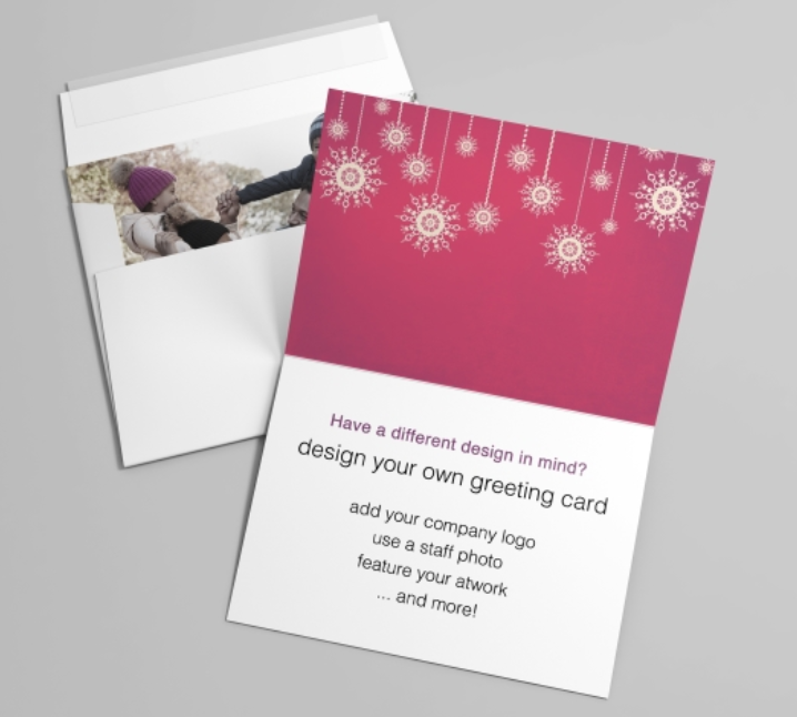 A an open greeting card with red, gold, and white holiday accents against an envelope with a photo card inside.