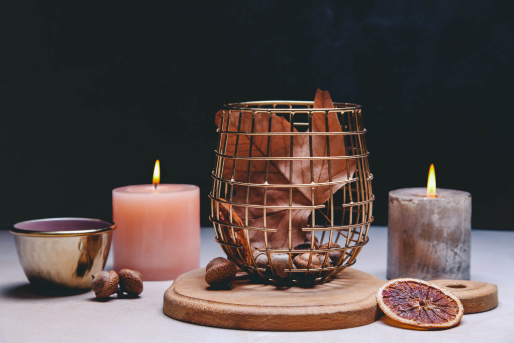 Beautiful burning candles and small cup of tea, autumn decor on black background.