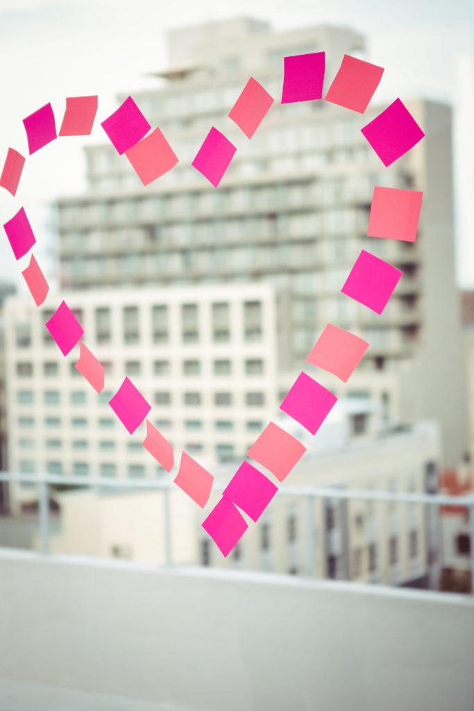 Heart in post-it on a window in office