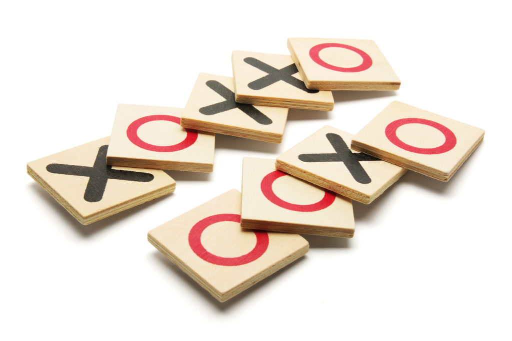 Tic-Tac-Toe Game on White Background with black Xs and red Os on light-colored wood blocks.
