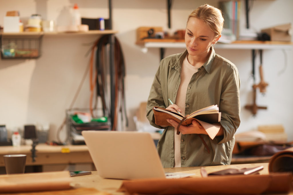 Horizontal shot of young female artisan looking at laptop screen writing something in her handmade notebook with leather cover