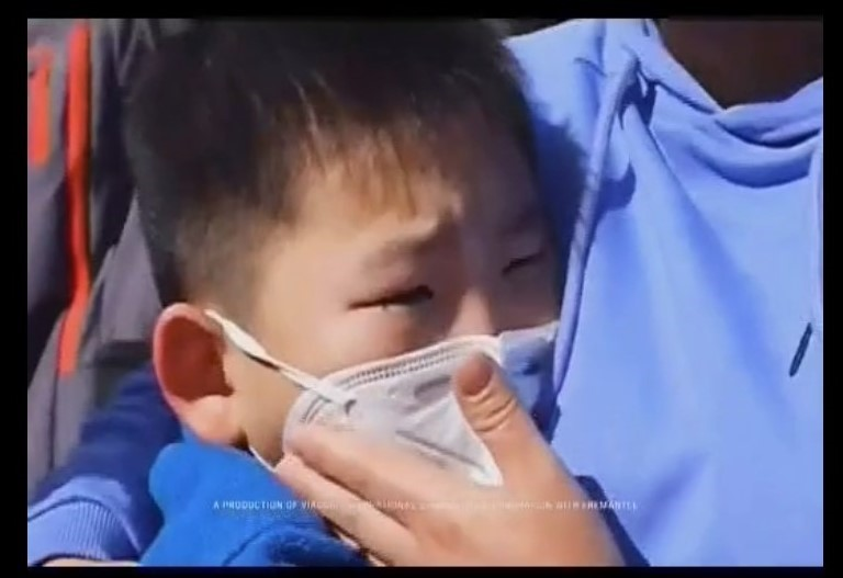 Asian child being hugged while wearing a face mask.