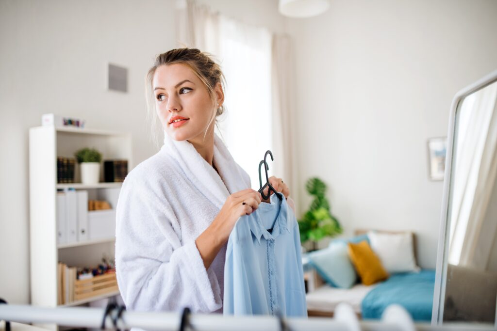A young woman indoors at home in the morning, choosing clothes to wear.