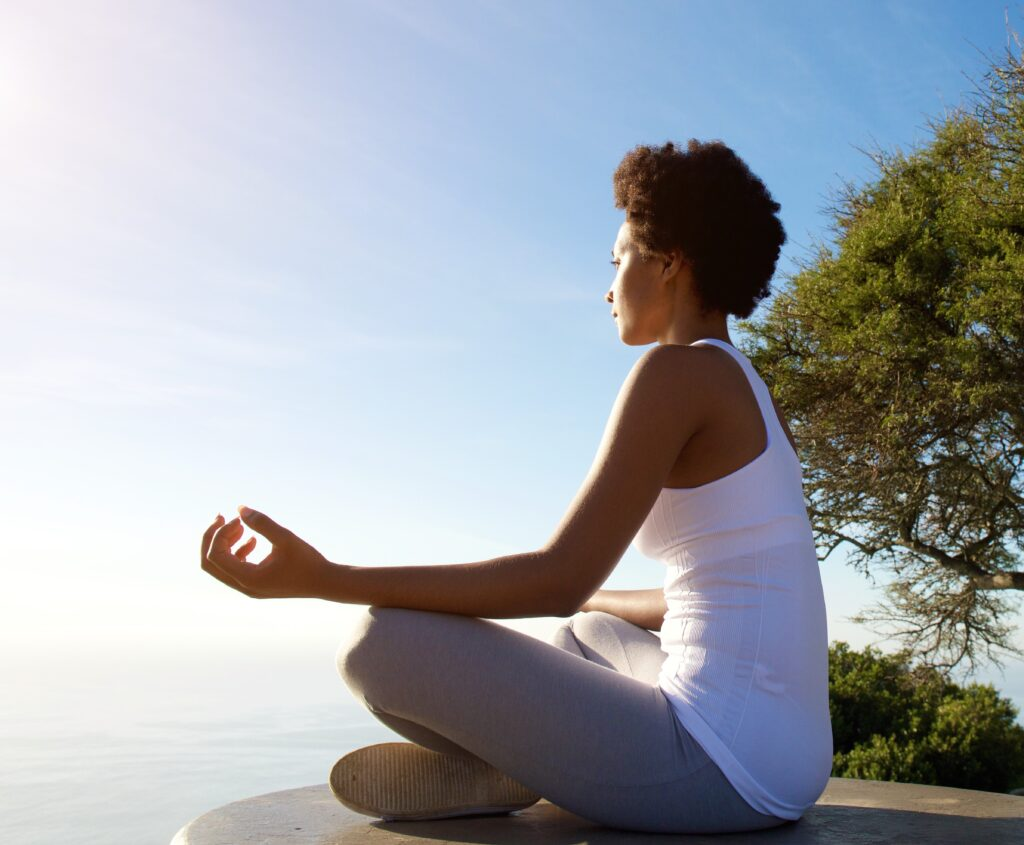 Side portrait of beautiful young woman sitting in yoga pose at beach