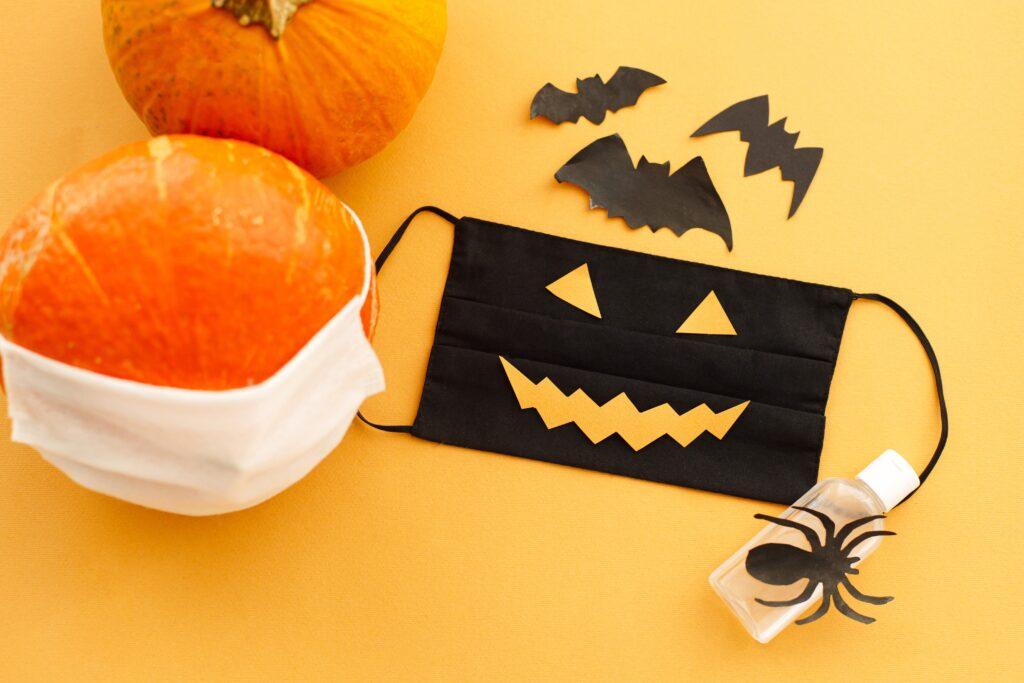 Halloween 2020 safe celebration. Evil face mask, pumpkin in mask, disinfection gel bottle, bat and spider decorations on orange background. Stay creative Stay safe